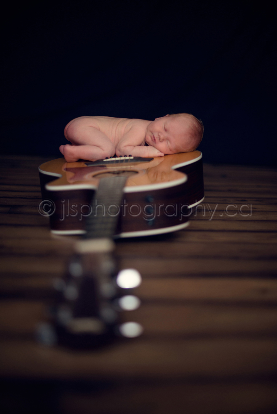 7 day old baby on acoustic guitar