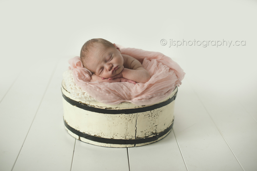 Chin pose, Newborn baby girl in a barrel, Baby girls face